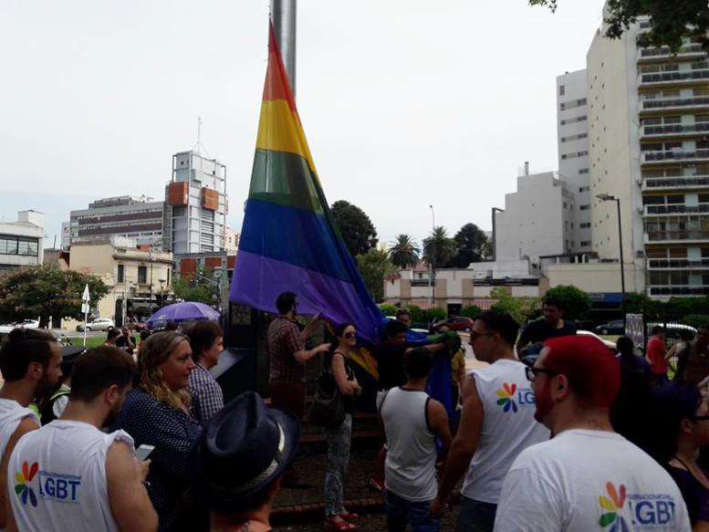 Izando la bandera de la Federación Argentina Lesbianas, Gays, Bisexuales y Trans en el mástil del parque Centenario.