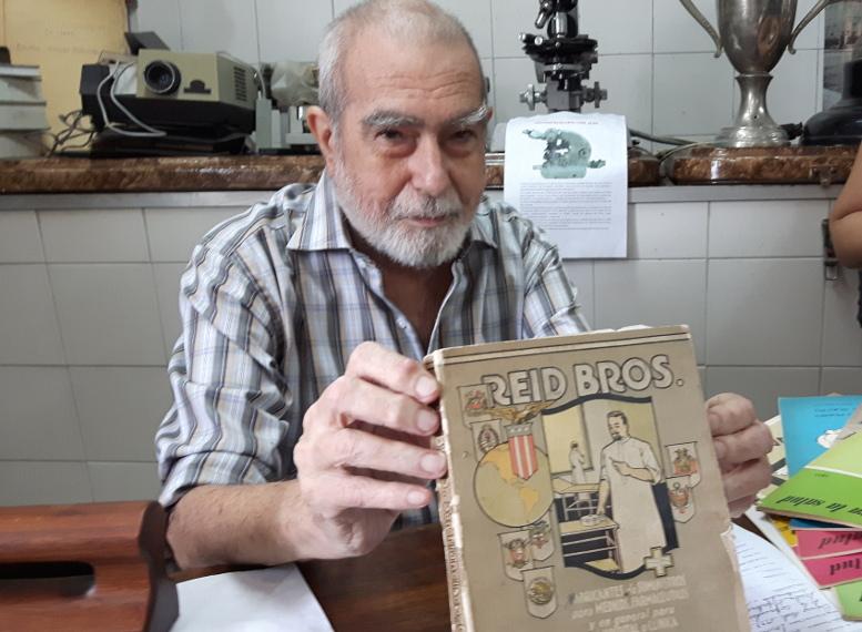 El Dr. Oscar Balbachán muestra uno de los libros de la colección del Museo