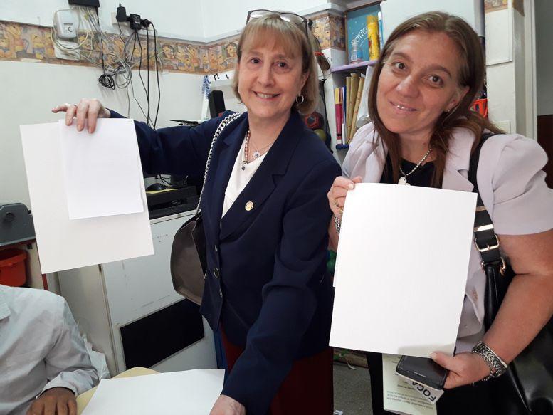 Susana Espósito y Fernanda Llorensi muestran trabajos realizados por los chicos en el papel para las impresoras Braille, donado al colegio recentemente
