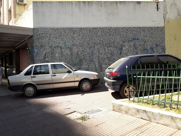 Autos estacionados en la vereda de la plaza.