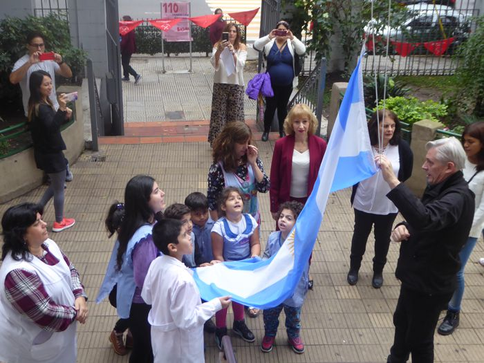 Izando la bandera en la entrada del colegio.