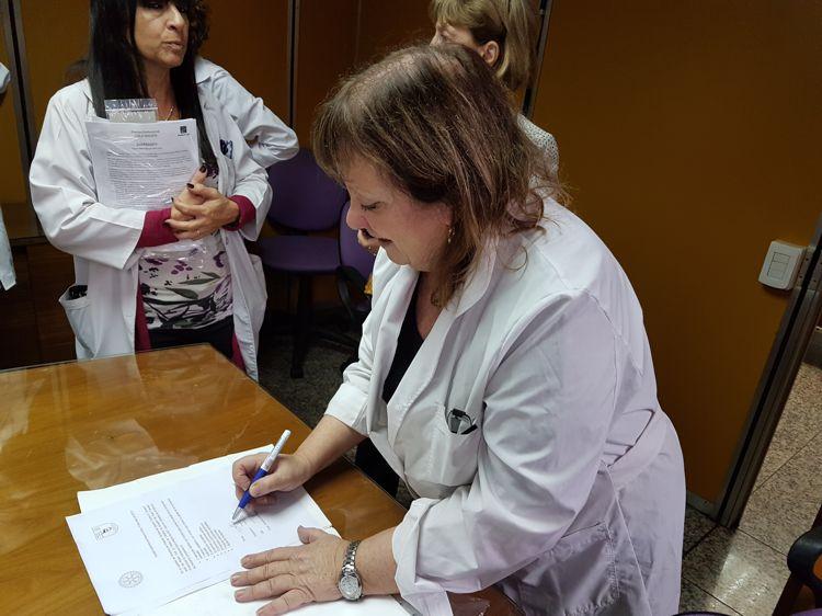 La Dra. Fernández Alonso firma la recepción de la donación.