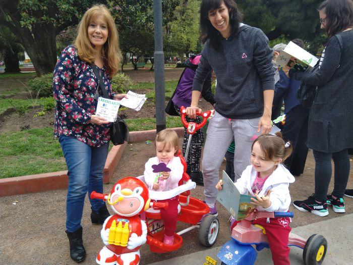 Liliana entregando libros a los más pequeños.