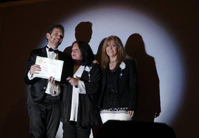 Marina Bussio y Liliana Arnaiz entregan el diploma por su labor solidaria a Diego Reinhold.