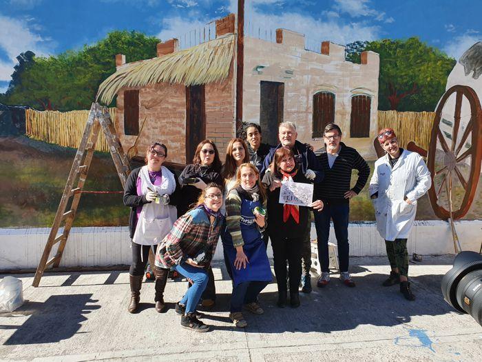 Darío Klehr y el grupo de artistas junto al mural. Los acompaña Marina Bussio, esposa de Héctor Núñez Castro, autor del dibujo original.