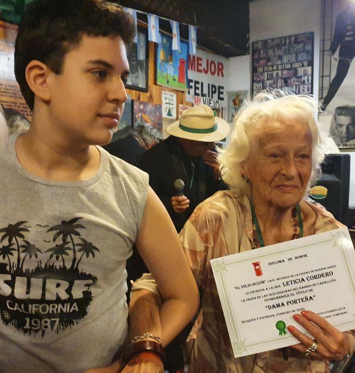 Leticia, vecina de 100 años, acompañada por su nieto Joaquín, con su diploma.