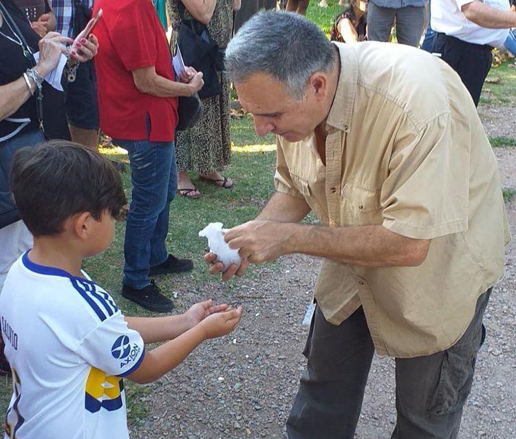 Sergio Mosquera, de la Asociación La Cofradía de Caballito reparte entre el público tierra traída del Campo de la Gloria de San Lorenzo que fue depositada junto al busto de San Martín.