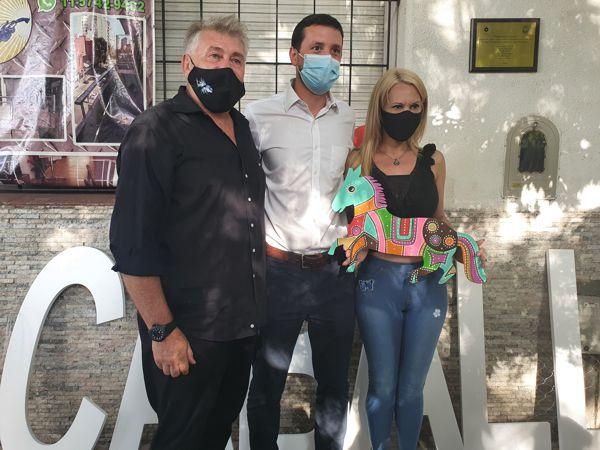 Darío Klehr y Federico Ballán entregan un Caballito a la propietaria de la casa.